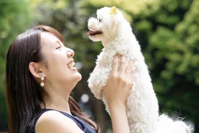 犬を抱き上げて笑顔の女性