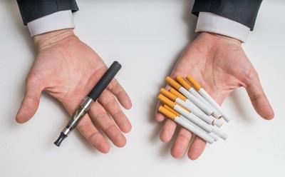 手のひらに乗せたタバコと電子タバコ