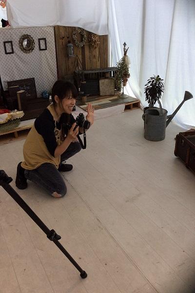 スタジオ内 女性 しゃがんでいる カメラ 手をかざしている