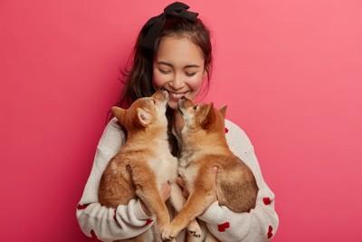 2匹の犬を抱く女性