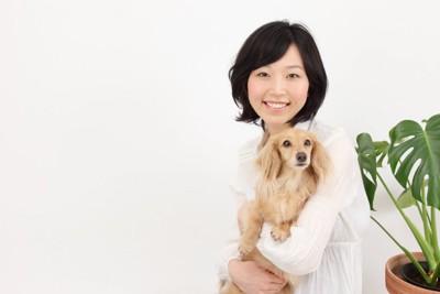 小型犬を抱く女性