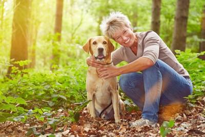 笑顔の女性と共に並ぶ犬