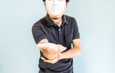 手を差し出す仮面を被った男性