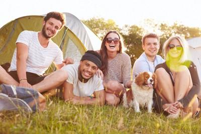 一緒にキャンプを楽しむ人たちと犬