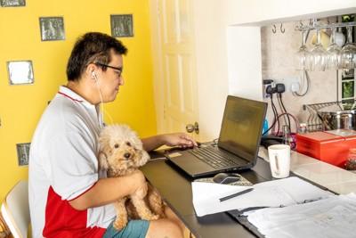 愛犬を抱いてリモートワークする男性