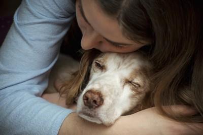 犬を後ろから抱きしめる女性