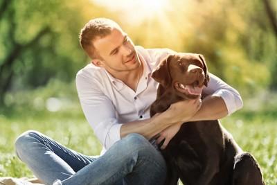 芝生に座りチョコラブを抱く男性