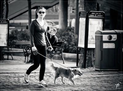 街を散歩する女性と犬