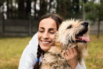 犬の後ろから抱きしめる女性