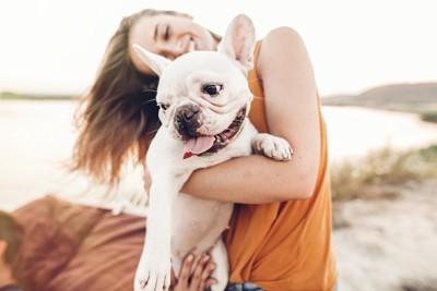 女性に抱かれる笑顔のフレンチブルドッグ