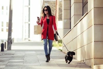 スマホを見ながら犬の散歩をする女性