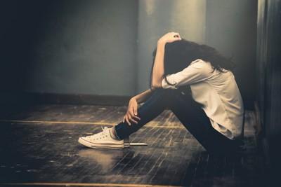 膝と頭を抱える女性