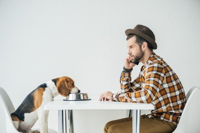 テーブルに座る犬と男性