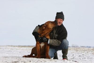 土佐犬と抱き合う男性の写真