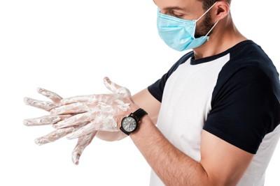 手を洗うマスクを着けた男性