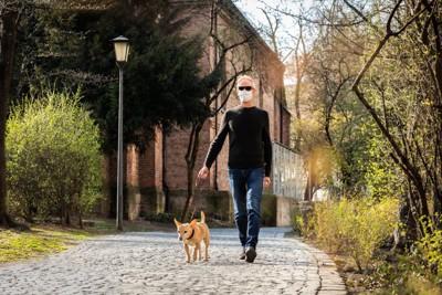 犬と散歩するマスクをした男性