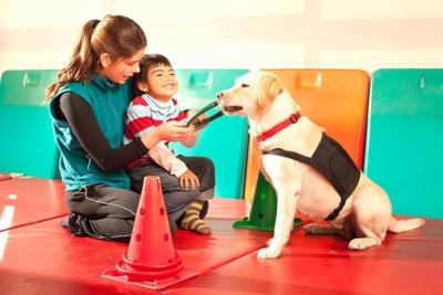 セラピー犬と遊ぶ女性と子供