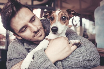 男性に後ろから抱っこされる犬
