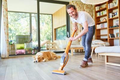 床に寝そべる犬と掃除機をかける男性