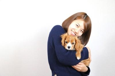 犬を抱っこする笑顔の女性