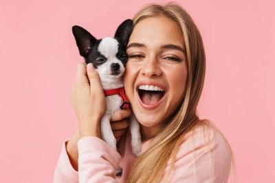 ピンクの背景と頬を寄せ合う犬と女性