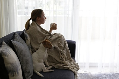 ソファーに一緒に座る女性と犬