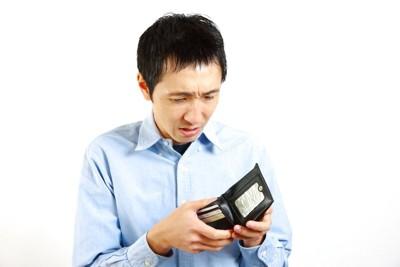 財布を見て困っている男性