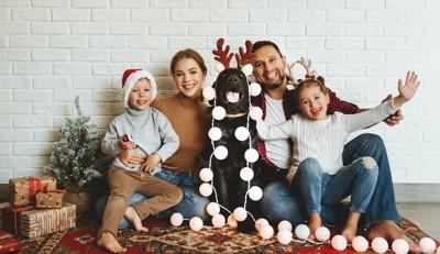 パーティーを楽しむ家族の真ん中に座る犬