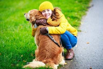 ゴールデンを抱きしめる女の子