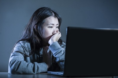 パソコンを見て肘をつく女性
