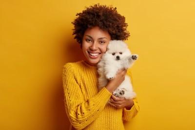 黄色い背景で子犬を抱く女性