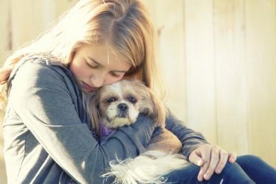 女性に抱かれる犬