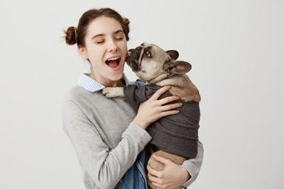 女性に抱き上げられるパグ