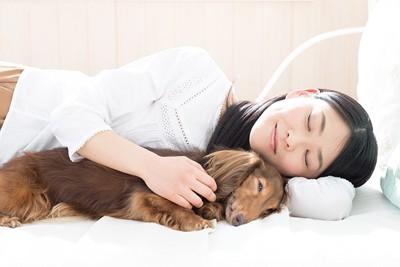 犬と一緒に寝ている女性