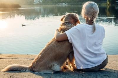 肩を寄せ合う女性と犬の後ろ姿