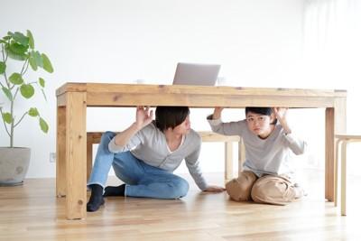 机の下に隠れる親子