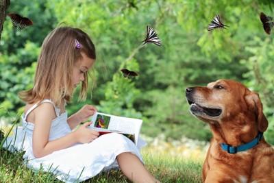本を朗読する少女とそれを聞いている犬
