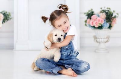 女の子にハグをされる子犬