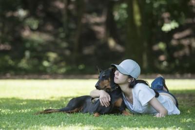 木陰で休憩する犬と女性