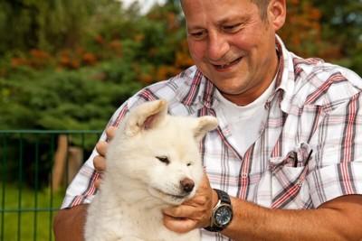 飼い主とスキンシップ中の秋田犬