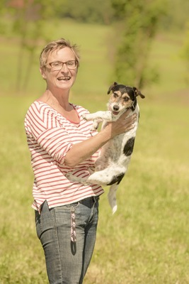 犬を抱っこするストライプの女性