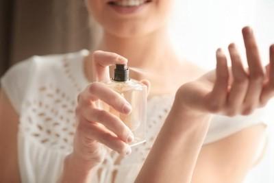 手首に香水をかけている女性