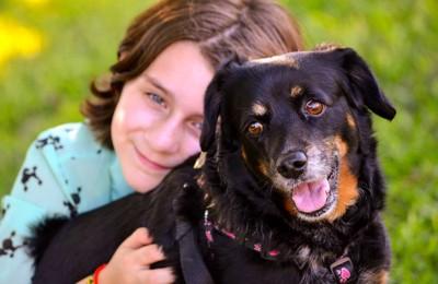 笑顔を見せる男の子と黒い犬
