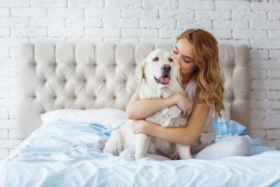 ベッドの上で犬を抱きしめる女性