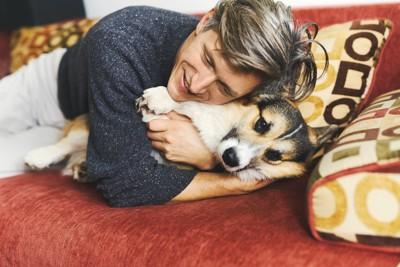 横になった犬に乗って抱きしめる男性