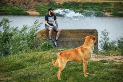 たばこを吸う男性とそれを見る犬