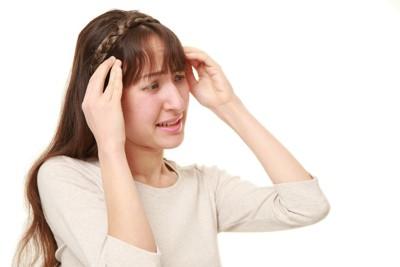 頭を抱えて悩んでいる女性
