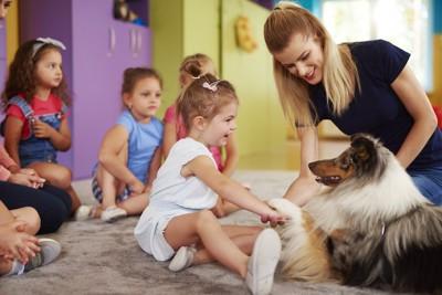 教室で犬と触れ合う子供たち