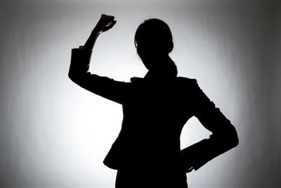 拳を振り上げる女性の影