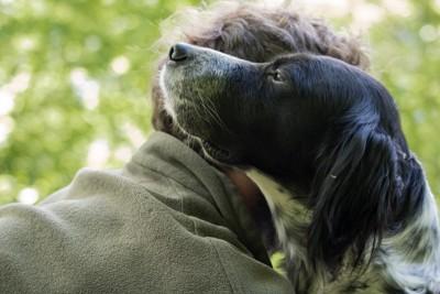 顔をくっつけあった犬と男性